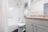Well lit white bathroom, with vanity sink and mirror, toilet and bathtub and shower with curtain.