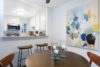 round table with 4 wooden chairs, colorful painting on the wall with breakfast bar and kitchen in the background.